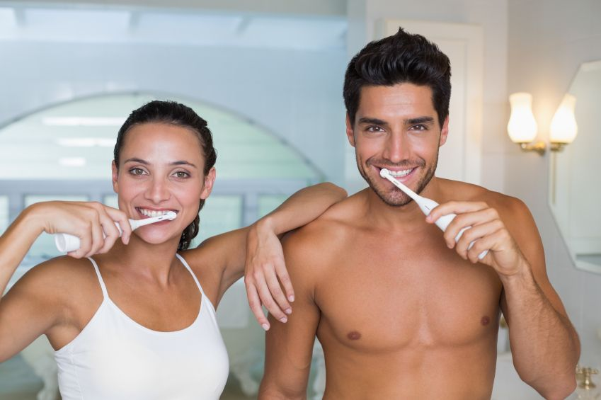 Atrractive young couple brush teeth at home in bathroom